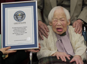 Japan's 114-year-old Misao Okawa poses with the Guinness World Records certificate of the world's oldest woman at a nursing home in Osaka, western Japan, Wednesday, Feb. 27, 2013. She has been recognized as the world's oldest woman by Guinness World Records on Wednesday. (AP Photo/Itsuo Inouye)